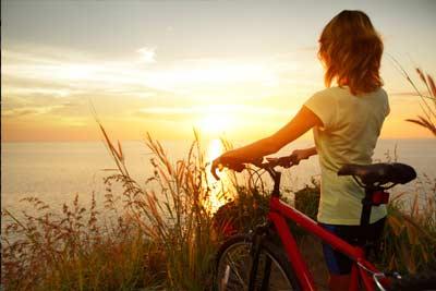 Woman on bike looking at ocean